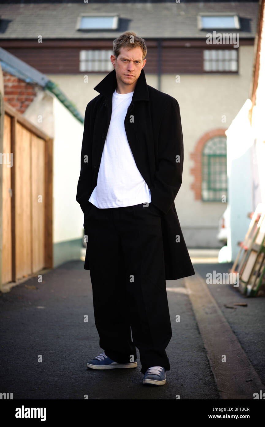 30 year old man standing alone in an alleyway with his hands in his pockets wearing black coat white t-shirt sneakers, - Stock Image