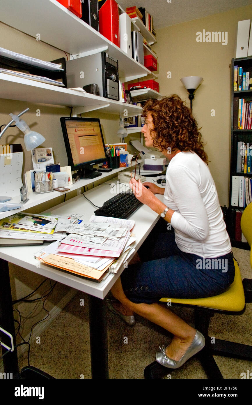 A 50-year-old self-employed woman works in her home office in Mission Viejo, California. - Stock Image