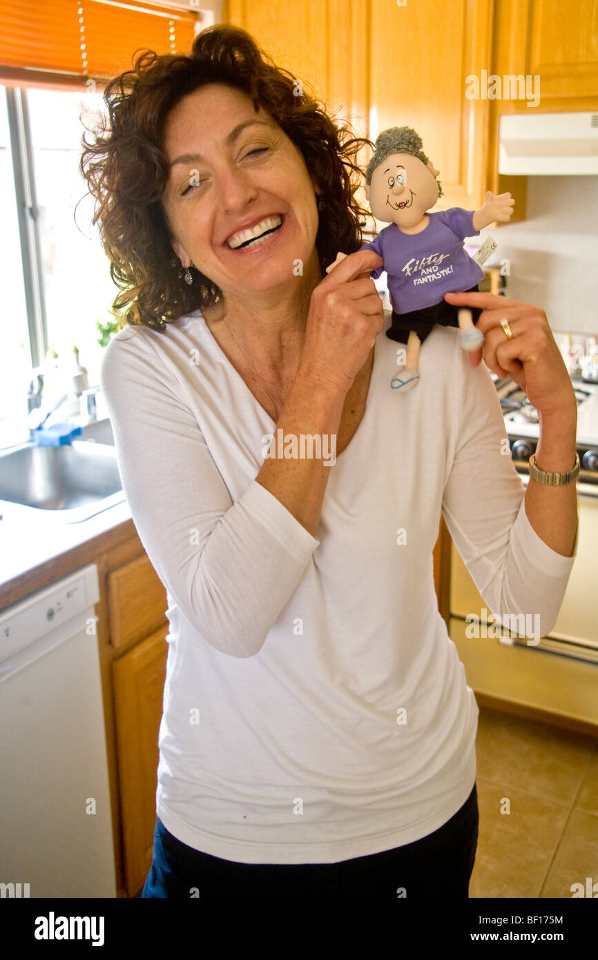 A 50 Year Old Woman Smiles Happily While Holding Fifty And Fantastic Doll Joke Gift At Her Birthday Party