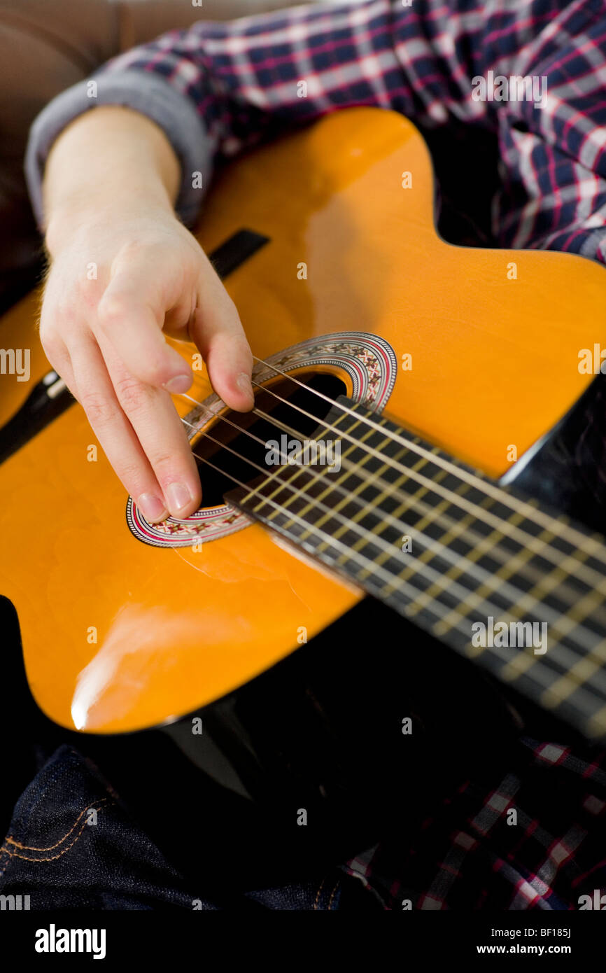 A teenager playing the guitar. - Stock Image