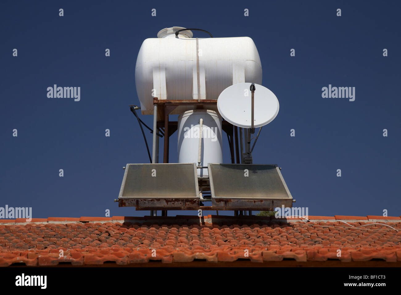 water tank feed and solar heating panels and satellite dish in republic of cyprus europe - Stock Image