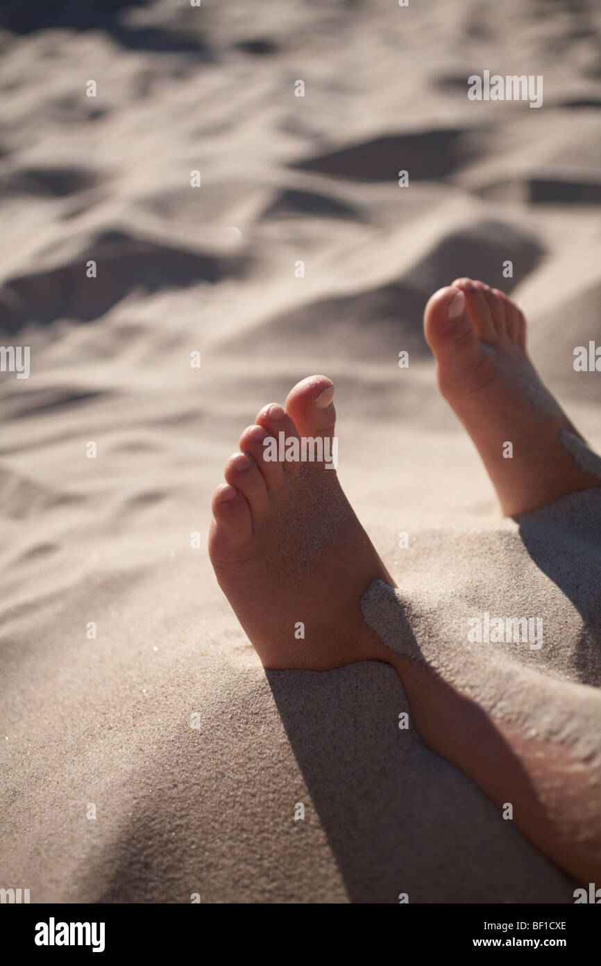 A boy covered with sand, Sweden. - Stock Image
