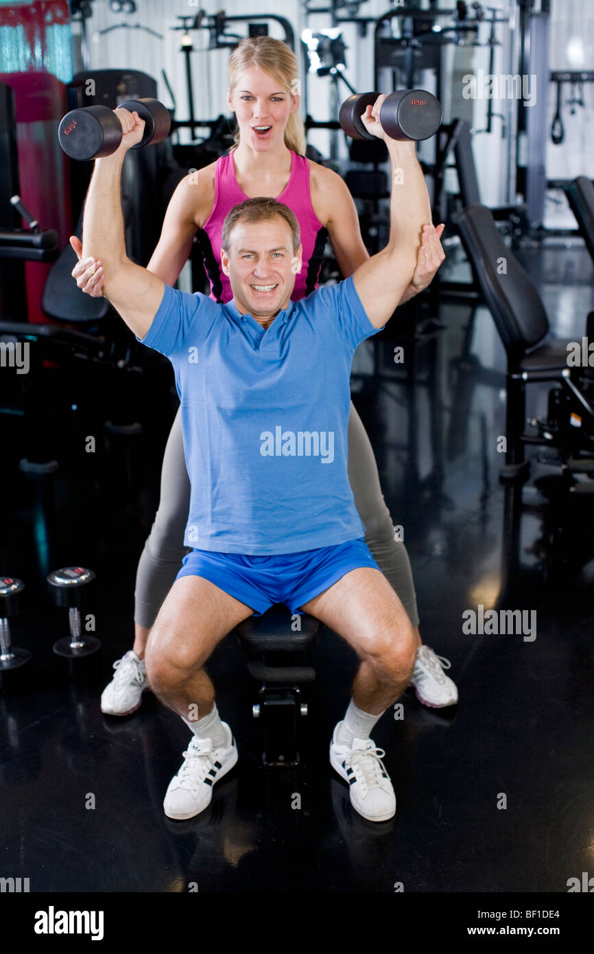 A man and a woman weight training at a gym, Sweden. - Stock Image