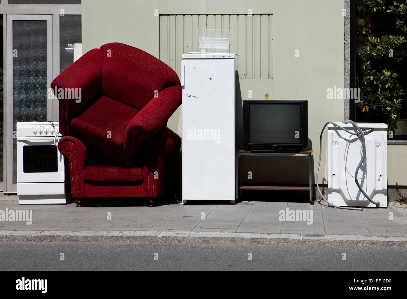 Furniture and appliances on a sidewalk waiting to be moved - Stock Image