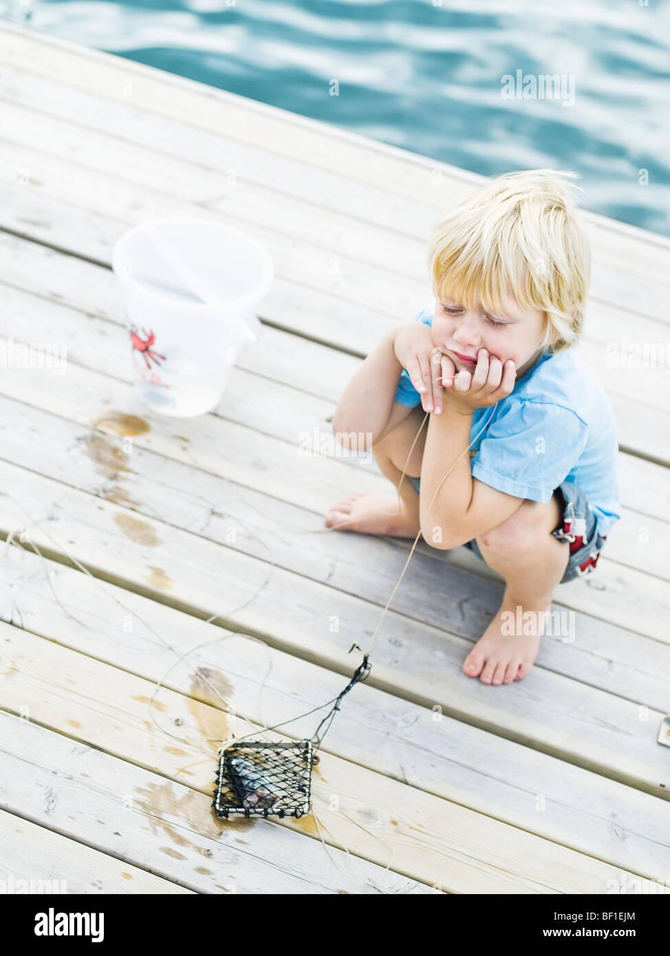 Scandinavian boy on a jetty, Sweden. - Stock Image