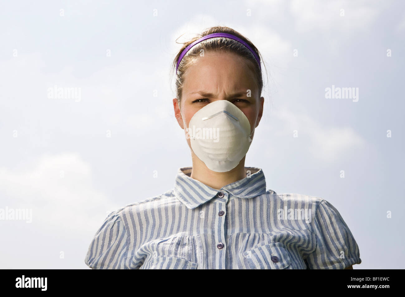 A young woman wearing a pollution mask - Stock Image