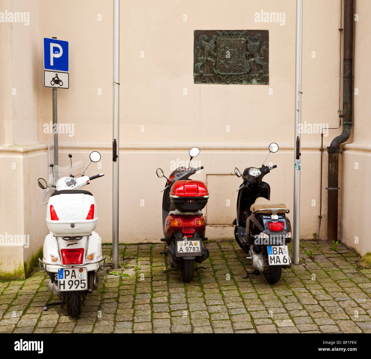 Three scooters parked in a scooter parking zone on an old street in Germany Europe - Stock Image