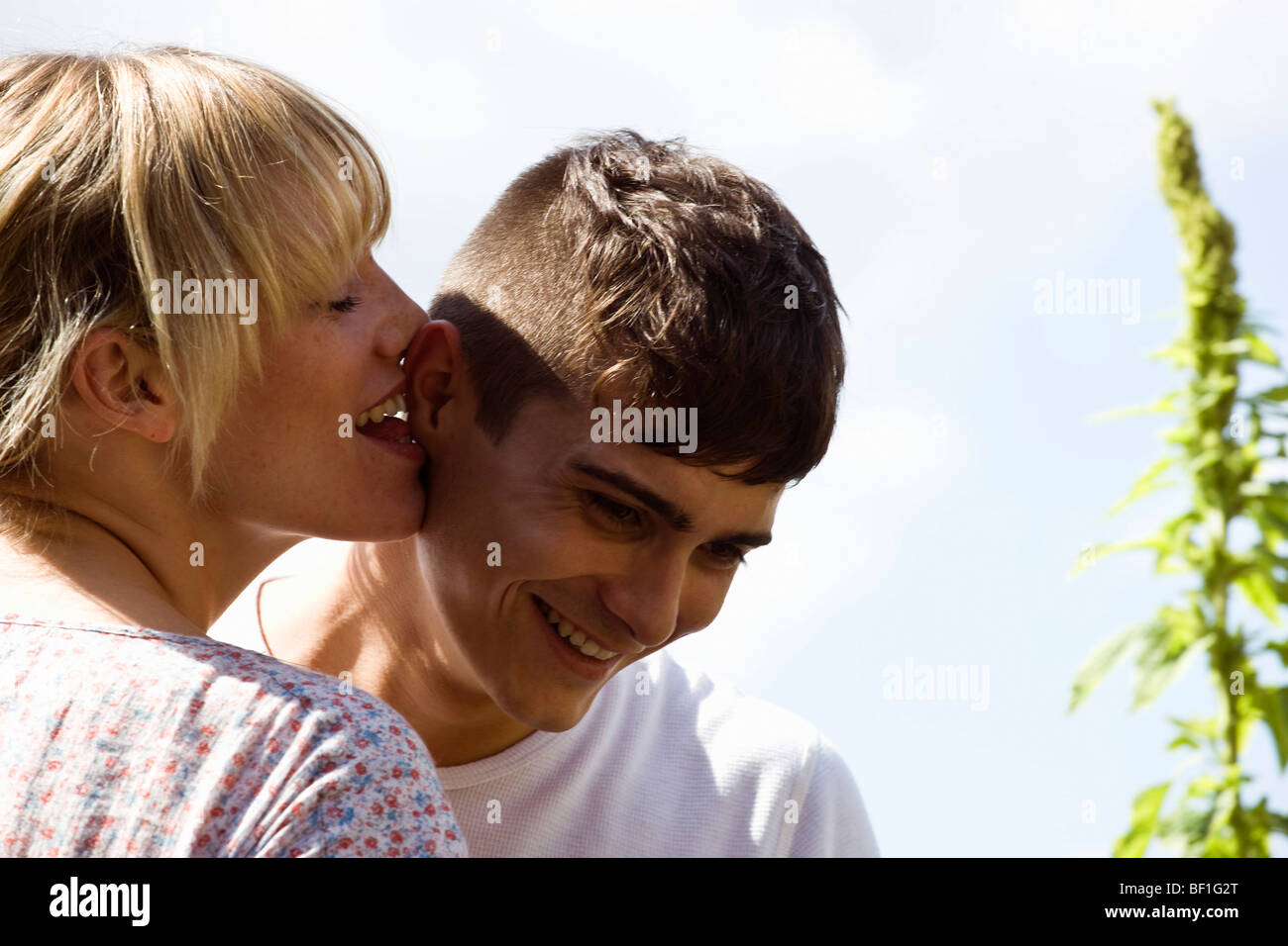 A young woman playfully licking a young man's ear - Stock Image