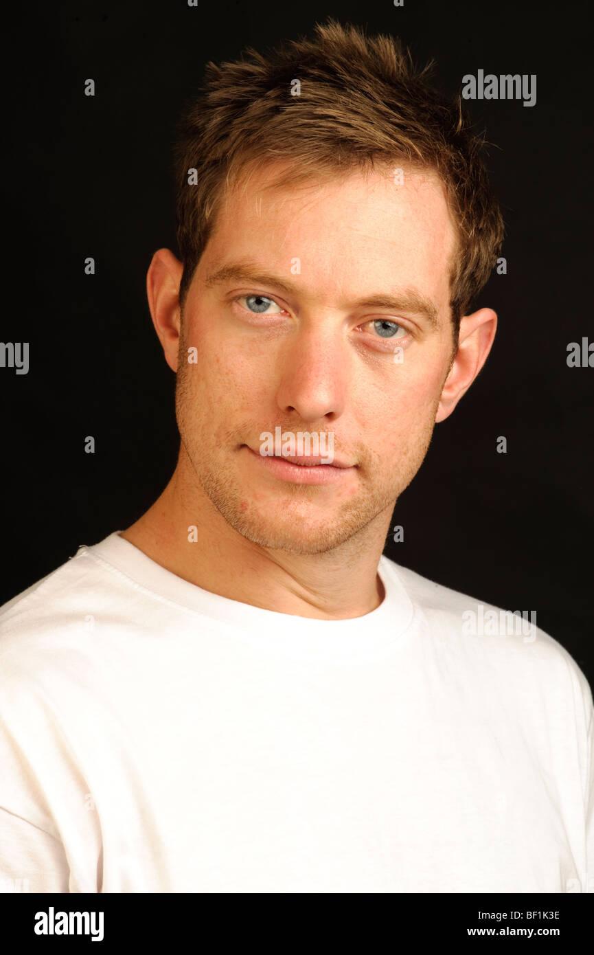Studio portrait of a 30 something year old blue-eyed English  British man wearing a white t-shirt - Stock Image