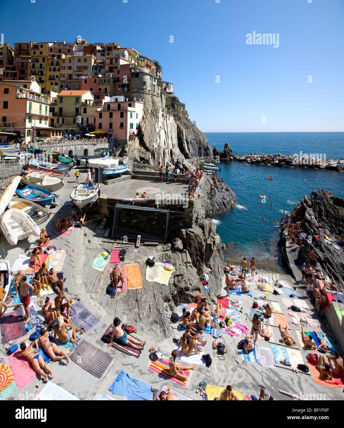 Riomaggiore with sunbathers on jetty, Cinque Terre, Liguria, Italy - Stock Image
