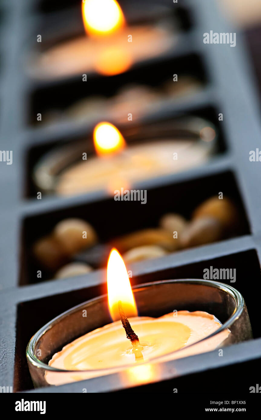 Burning candles in glass holders and wooden stand - Stock Image