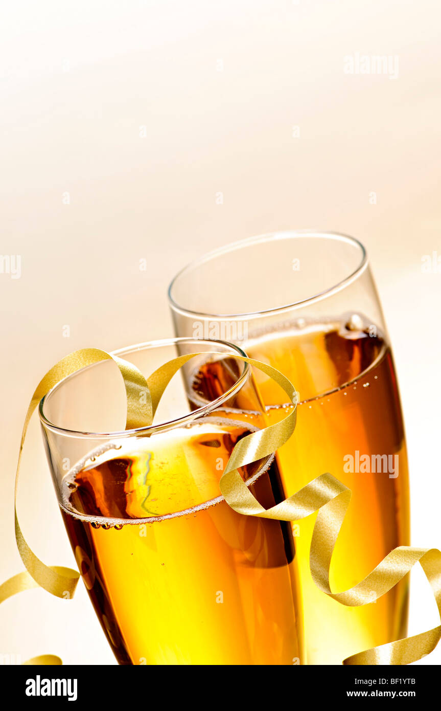 Two full champagne flutes with sparkling wine and ribbon - Stock Image