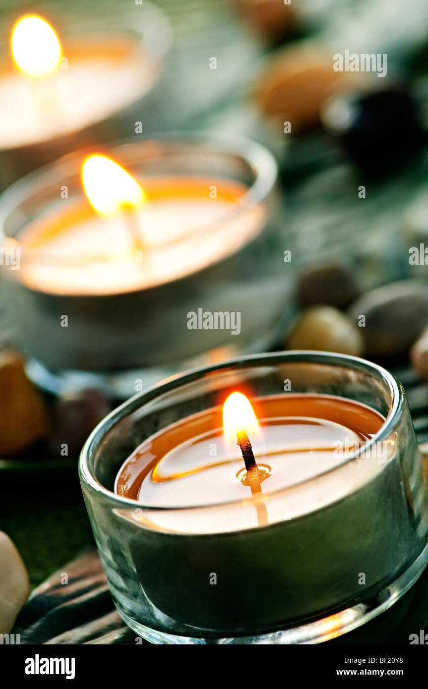 Burning candles in glass holders on green leaf Stock Photo