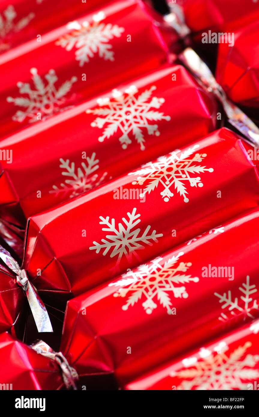 Closeup of many red Christmas crackers in a row - Stock Image