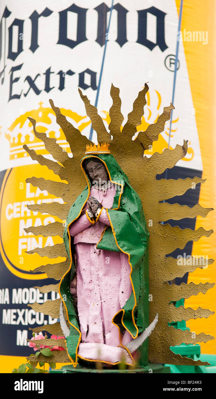 Religious sculpture in front of inflatable beer bottle at the Corona brewery in Guadalajara, Mexico. - Stock Image