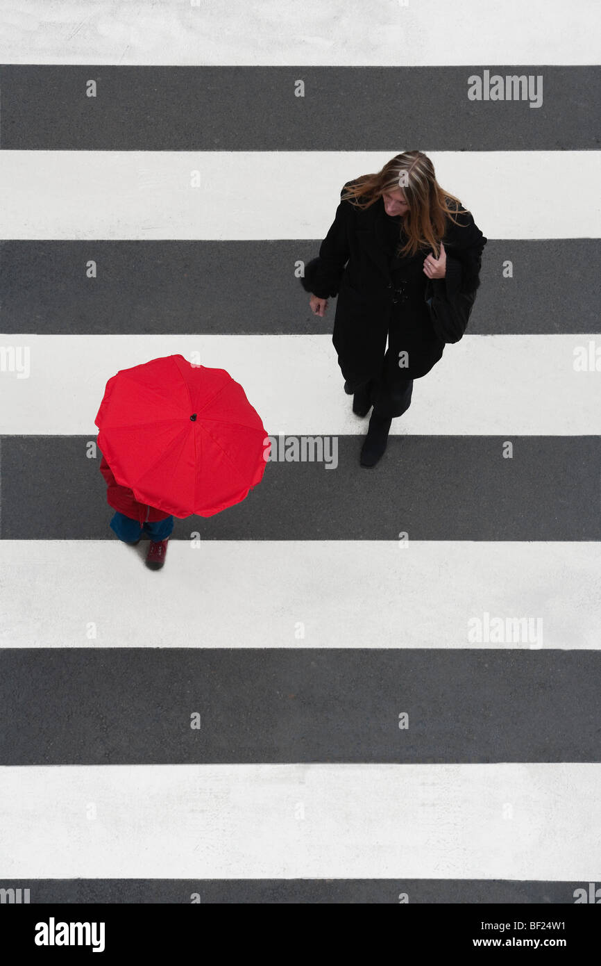 mother watching her child with red umbrella crossing the street - Stock Image