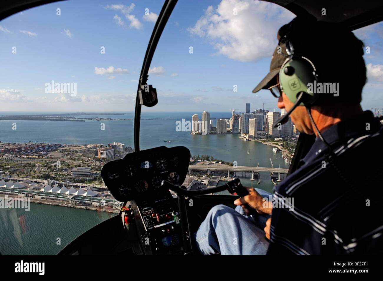 Pilot in a helicopter with view at Dodge Island and Downtown Miami, Miami, Florida, USA - Stock Image