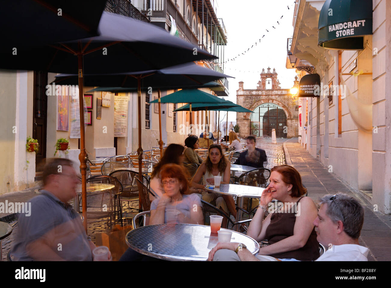 People sitting under sunshades in front of the cafe at Calle de Christo, San Juan, Puerto Rico, Carribean, America - Stock Image