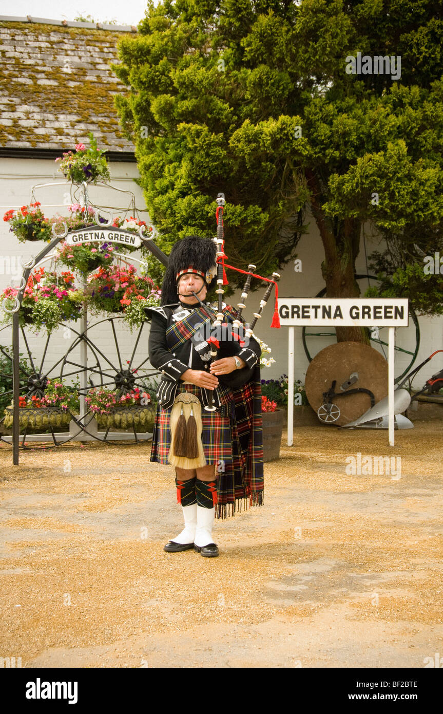 Piper playing bagpipes at Gretna Green, Scotland. - Stock Image