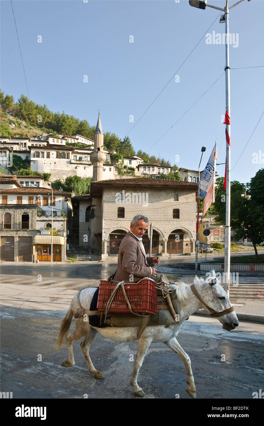 An albanian on a mule passes the Bachelors' mosque in the Mangalemi district of Berat , central Albania - Stock Image