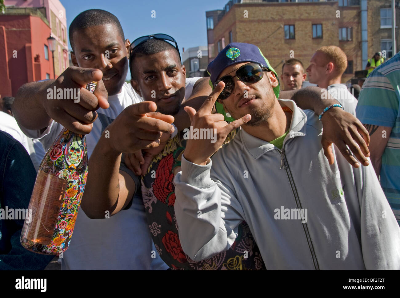 Three young men using hip hop or gangsta gestures in streets of Notting Hill - Stock Image