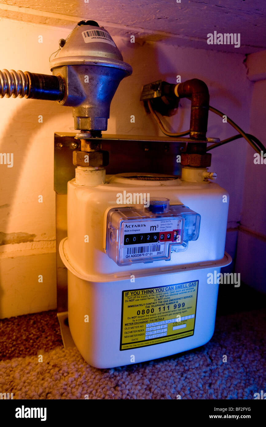 English domestic gas meter close up dial numbers reading measure house flat cupboard stair leak pipe measure quantify - Stock Image