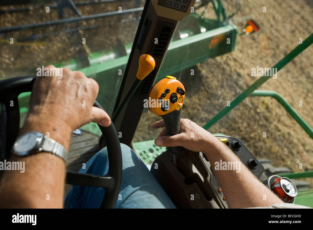 Agriculture - The hands of a farmer operating the controls of a combine during the soybean harvest / Northland, - Stock Image