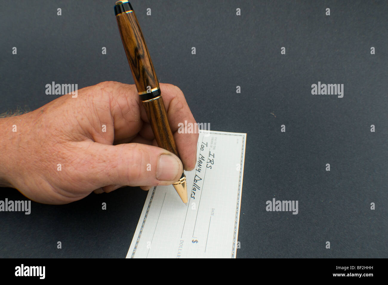 male hand writing check to IRS for Too many dollars - Stock Image