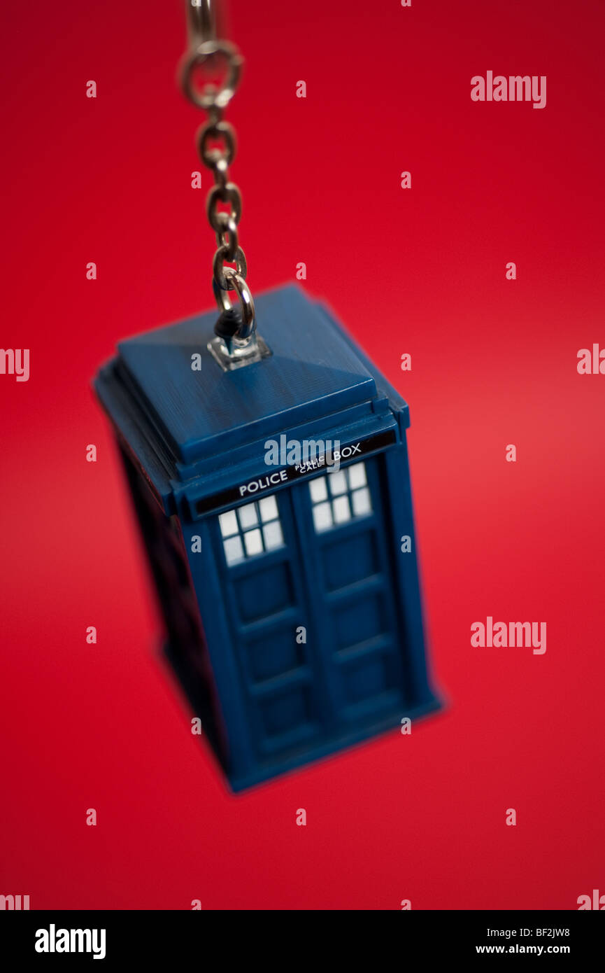A Doctor Who Tardis keyring hangs in front of a background. - Stock Image