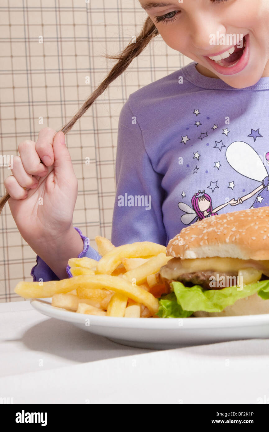 Girl looking at a plate of burger and French fries - Stock Image