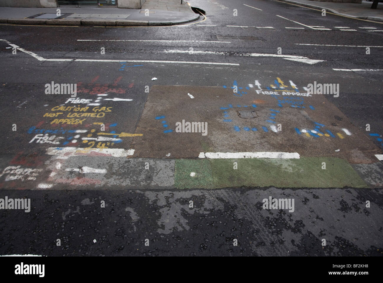 Road with markings for pipes and utilities painted on it - Stock Image