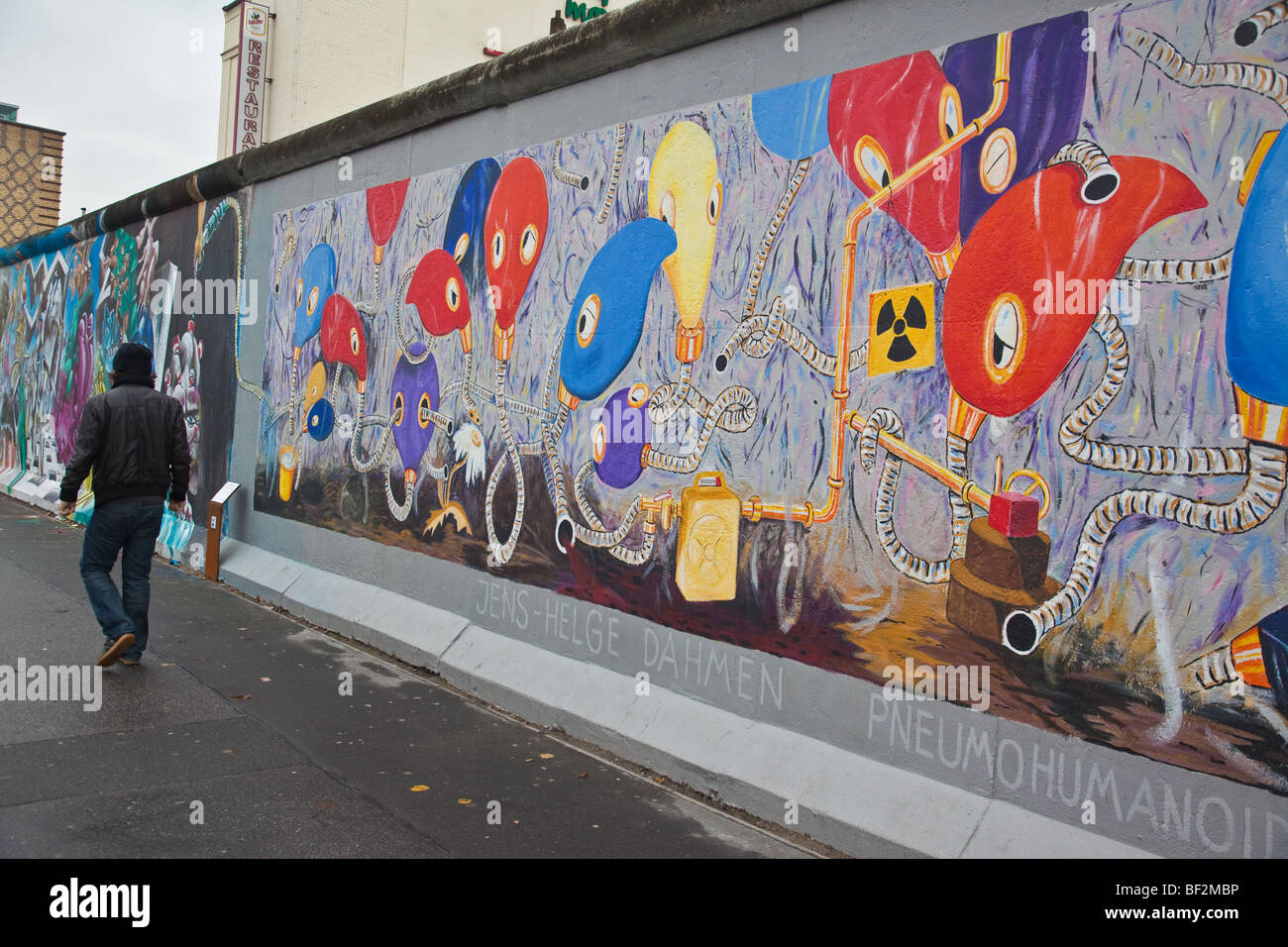 Newly repainted mural with a man walking past the Berlin Wall at East Side Gallery in Kreuzberg Berlin - Stock Image