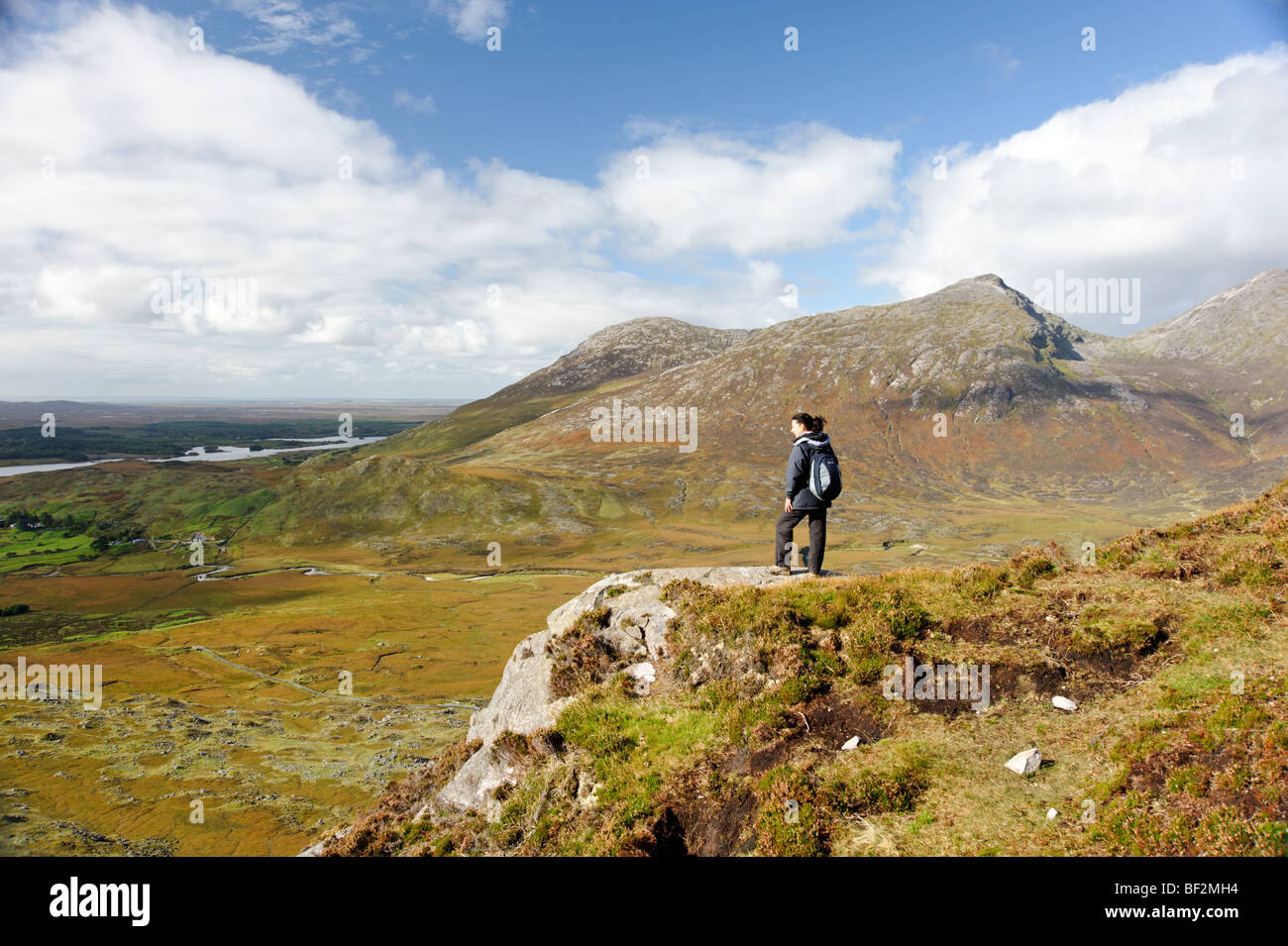 Hiker on Derryclare mountain with view to Benlettery, part of Twelve Bens mountain range. Connemara. Co Galway. - Stock Image