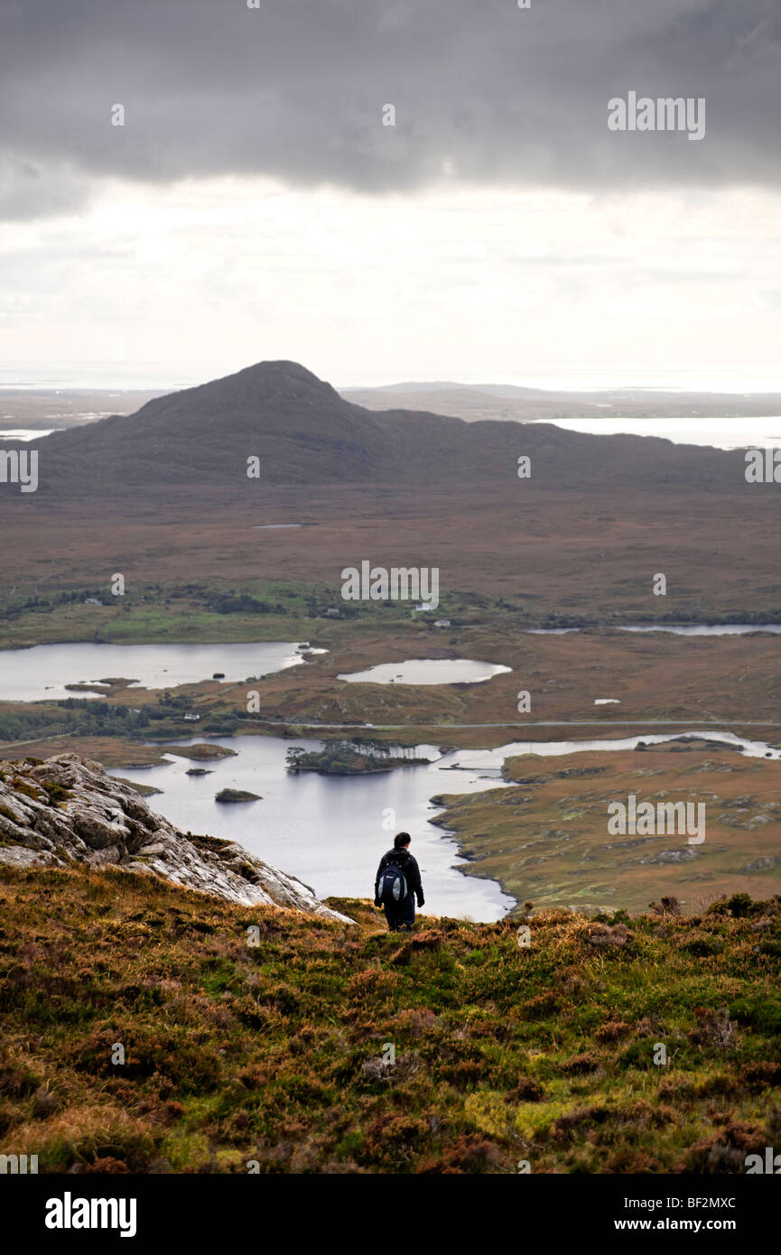 Hiker descending Derryclare mountain with view to lakes, part of Twelve Bens mountain range. Connemara. Co Galway. - Stock Image