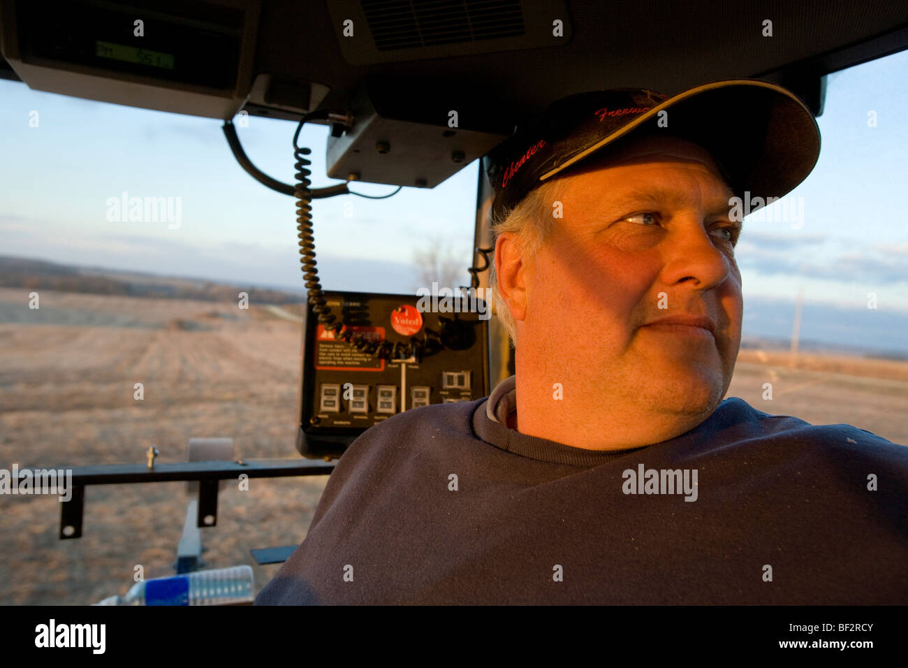 A farmer looks out from the inside of a tractor cab during the Autumn grain corn harvest / near Northland, Minnesota, - Stock Image