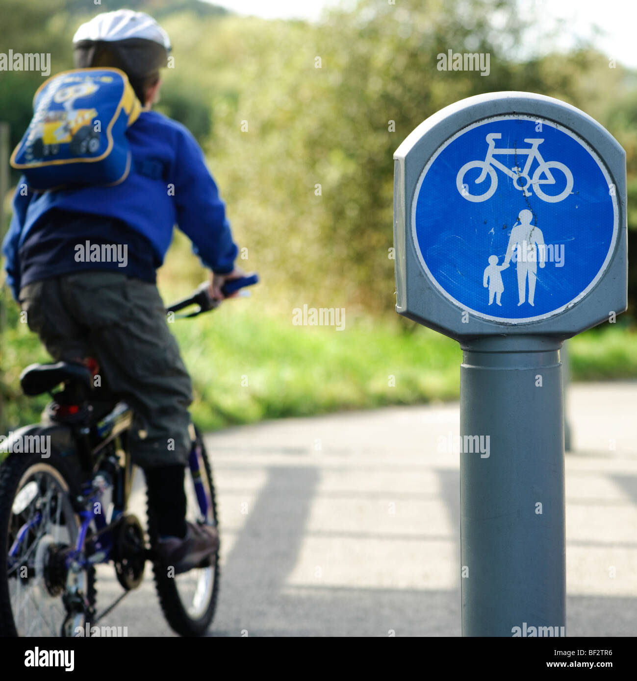 Rear view of a young Child cycling to school  on dedicated cycle path, UK - Stock Image