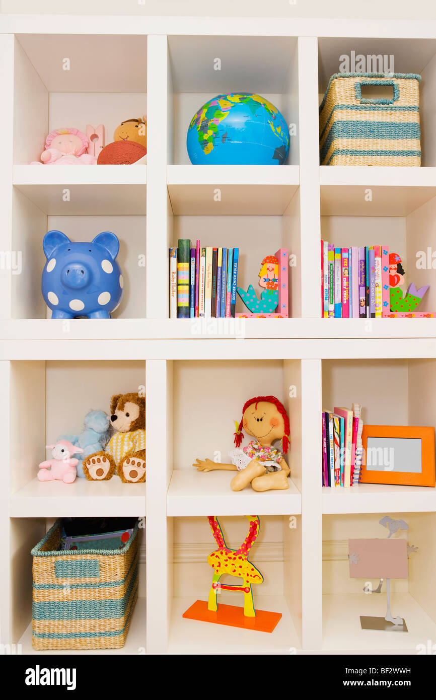 Books and toys on a shelf - Stock Image