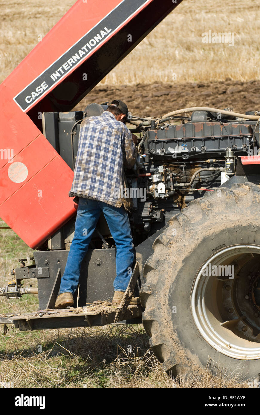 A farmer performs maintenance on a tractor in the field during planting season / near Pullman, Palouse Region, Washington, - Stock Image