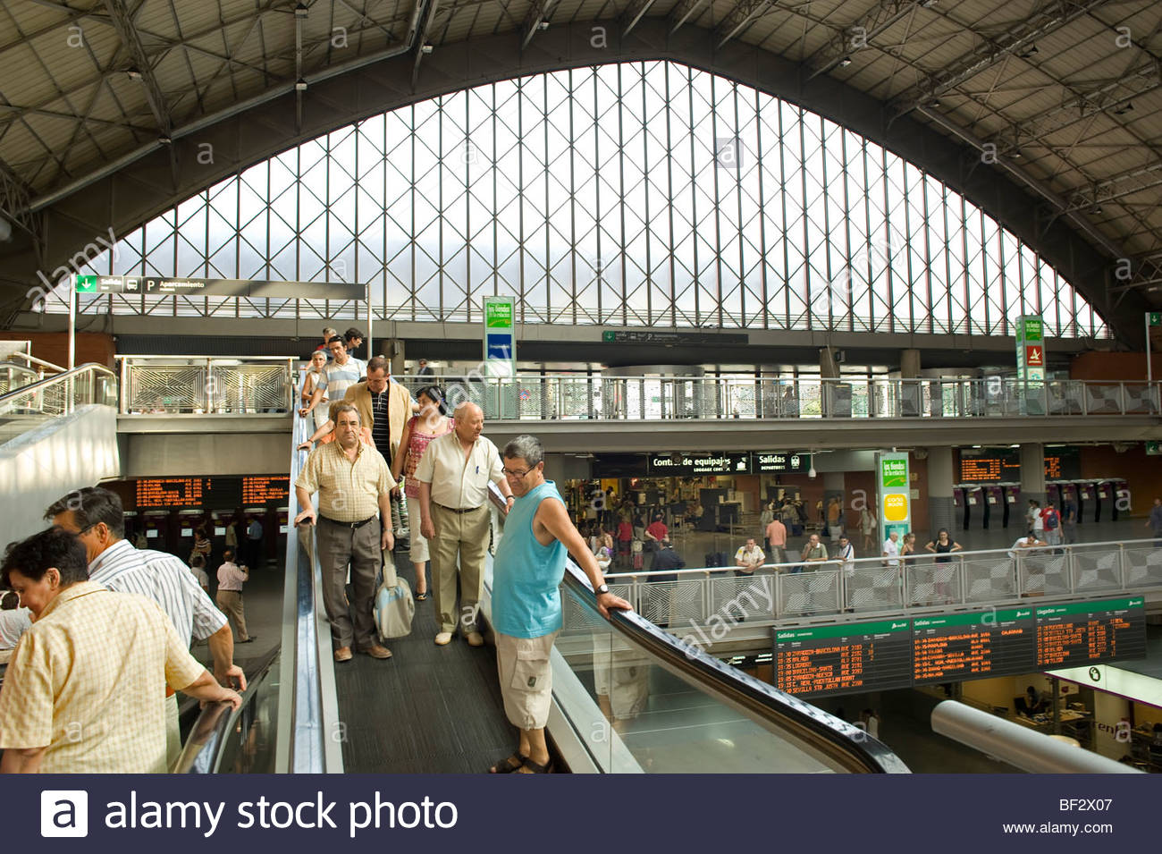 Travellers on an escalator at Atocha Railway Station in Madrid in Spain - Stock Image