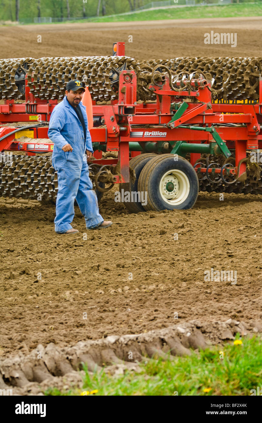 A field worker checks a mulcher to make sure it's prepared properly to be moved to another field / Burlington, Washington, - Stock Image