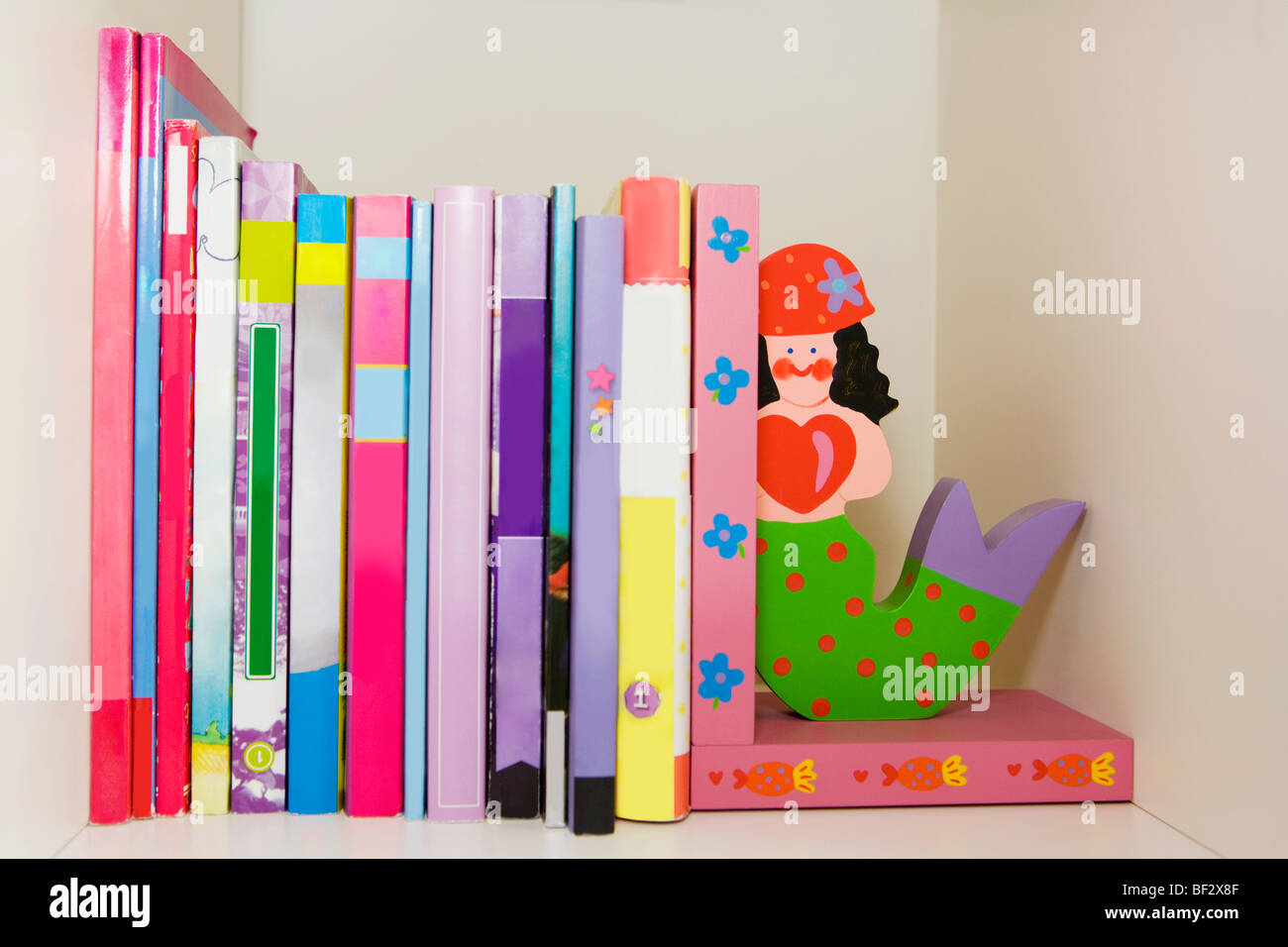 Close-up of books and toy mermaids on a shelf - Stock Image