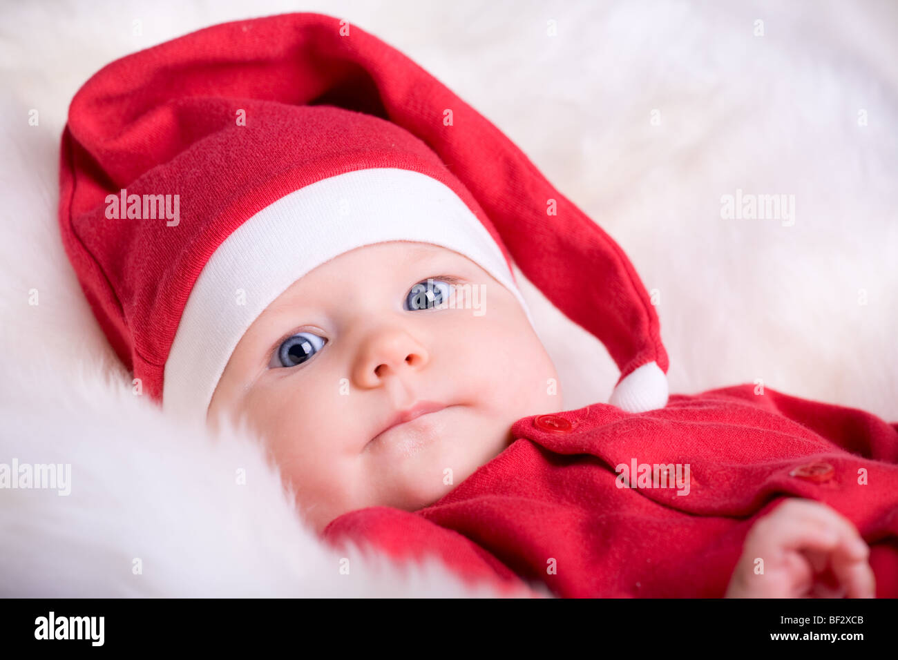 1d2657c6fa5 Portrait of Christmas baby girl in red Santa hat - Stock Image