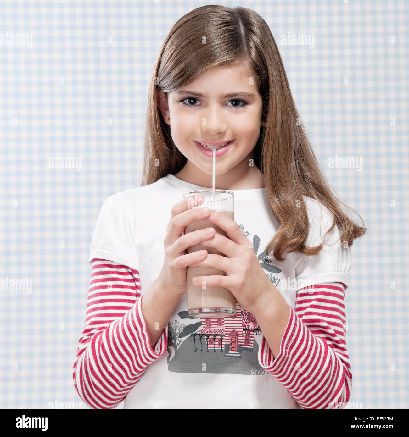 Girl drinking milk with a straw - Stock Image
