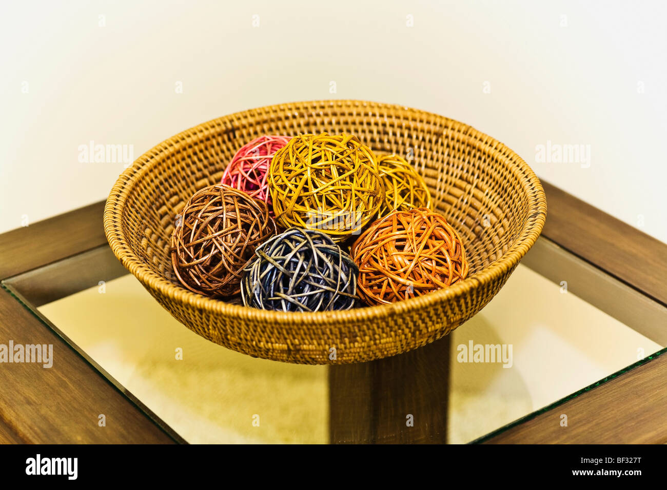 Decorative balls in a wicker basket on a table - Stock Image
