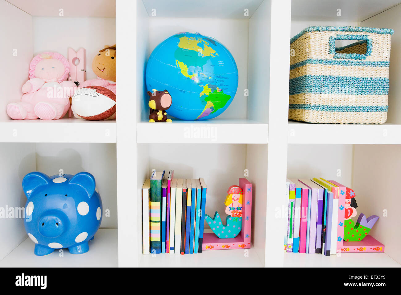 Toys and books on a shelf - Stock Image