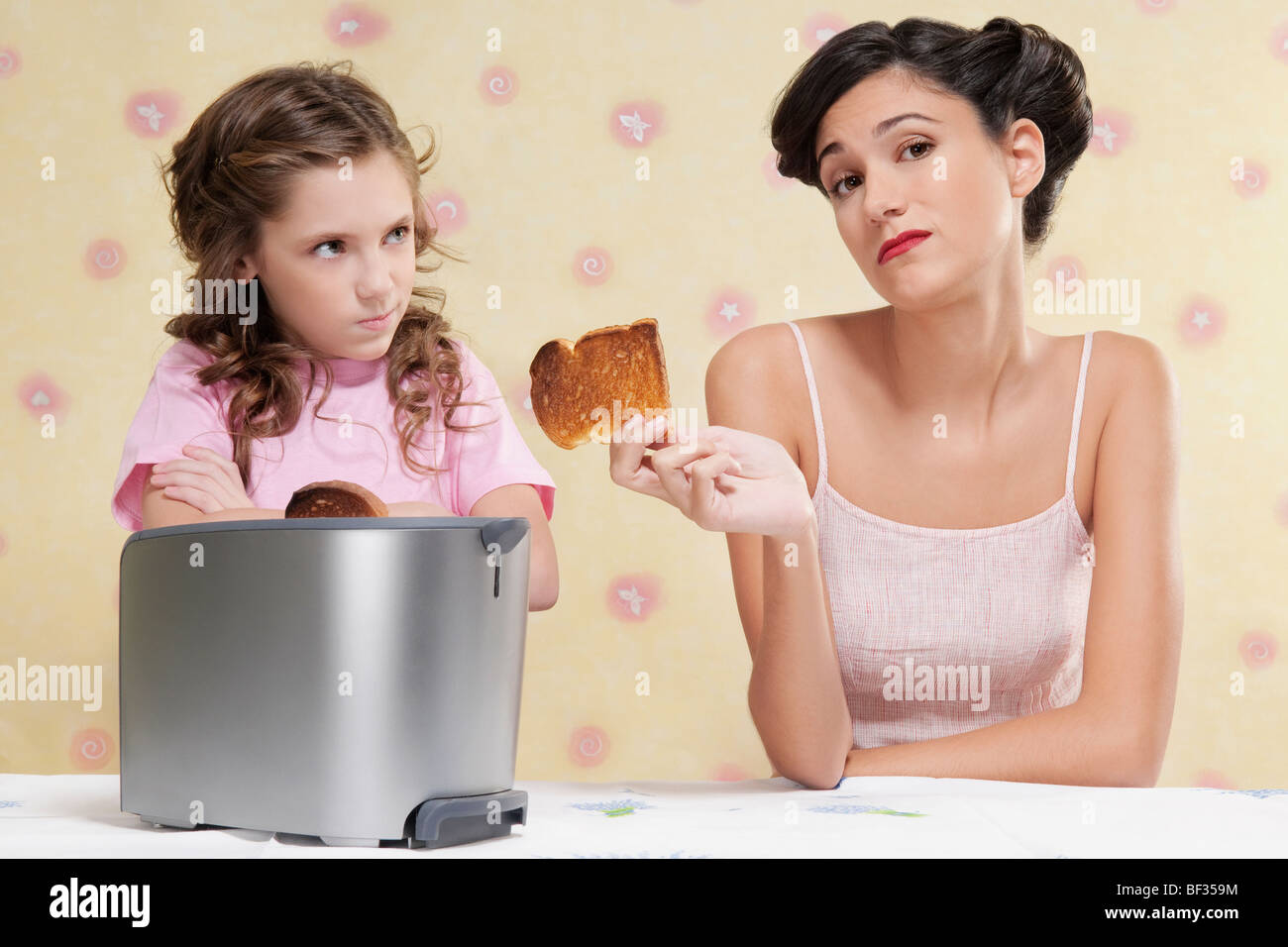 Woman giving her daughter a burnt toast - Stock Image