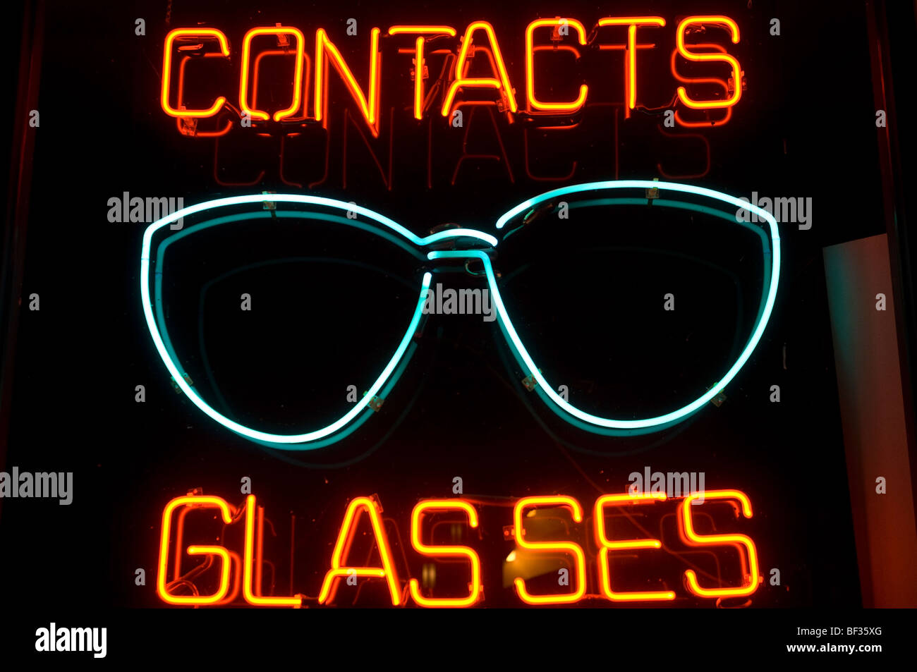 A sign in the window of an optometry office advertises contacts and glasses in bright neon lights visible in this - Stock Image