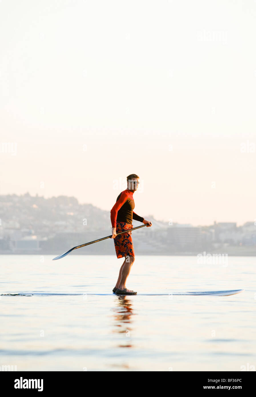 An athletic man paddling out on Elliott Bay early in the morning across from the downtown Seattle waterfront. - Stock Image