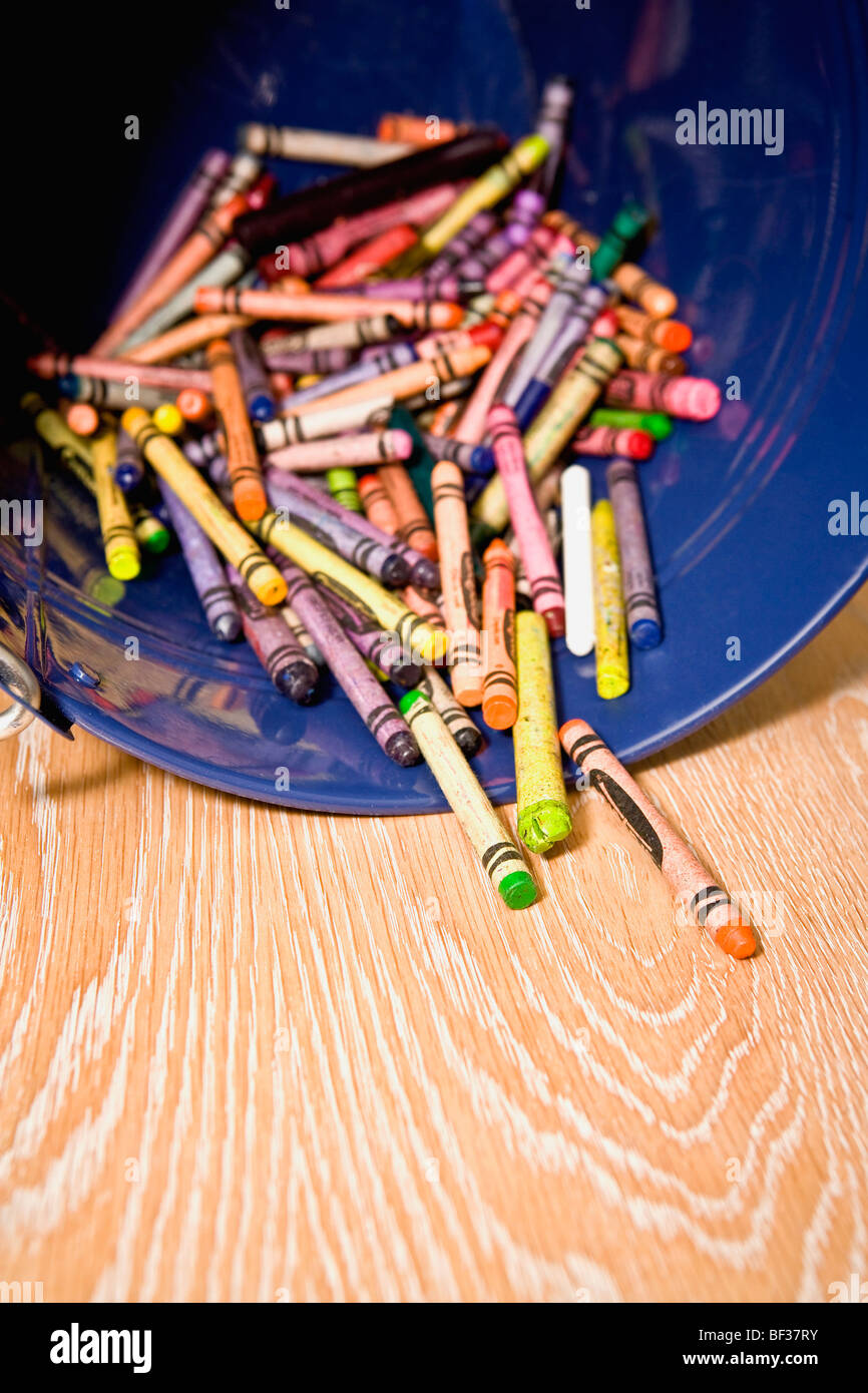 Close-up of crayons spilling out from a container - Stock Image
