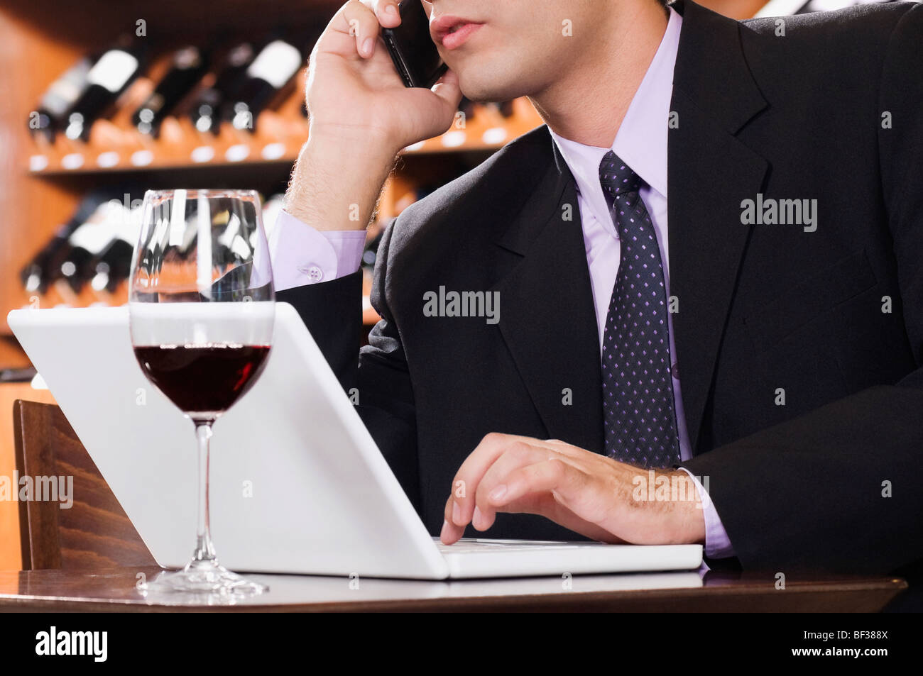 Businessman talking on a mobile phone in a bar - Stock Image